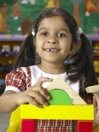 South Asian Indian girl playing with toys in nursery school