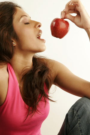South Asian Indian teenager girl wearing pink backless top trying to eat fresh red apple suggesting secret of her health