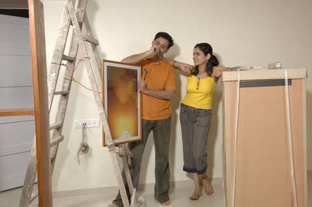 South Asian Indian man and woman thinking about photo frame in new flat