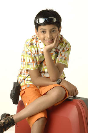 South Asian Indian boy of ten years old going on holiday taking camera and sitting on suitcase Stock Photo