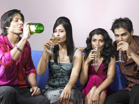 nightspot: South Asian Indian men and women drinking champagne celebrating party