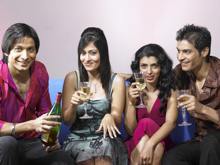 nightspot: South Asian Indian men and women showing champagne glasses  celebrating party