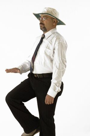 South Asian Indian cricket umpire indicating leg bye sign by hand touching raised knee Stock Photo
