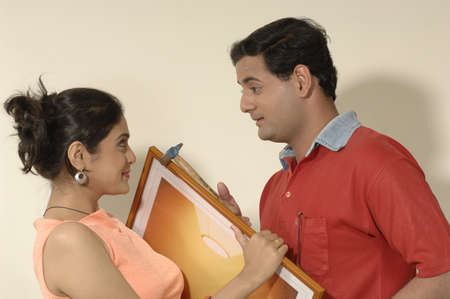 contemporary living room: South Asian Indian man and woman holding photo frame and hammer looking at each other in new flat