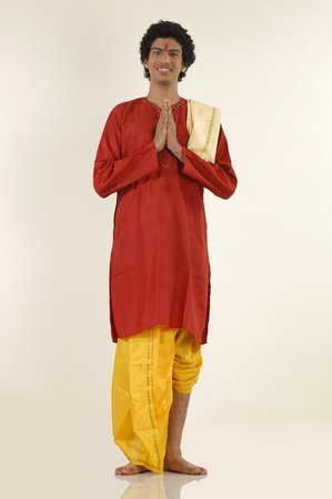 dhoti: South Asian Indian teenager boy wearing traditional yellow silk dhoti red long kurta doing Namaskar,Bombay Mumbai,Maharashtra,India