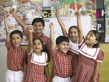 South Asian Indian boys and girls standing together with raising hands in nursery school