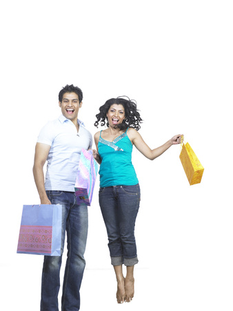 South Asian Indian man and woman holding shopping bags and jumping with joy