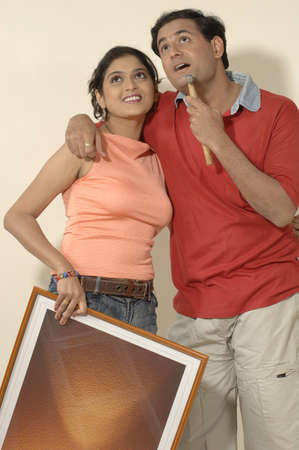 contemporary living room: South Asian Indian man and woman holding photo frame and hammer standing close to each other looking above in new flat LANG_EVOIMAGES