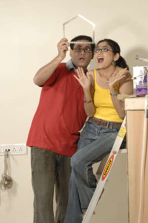 South Asian Indian man and woman looking at folding ruler as home in new flat Stock Photo