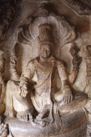 Sculpture of Vishnu seated on sesha in Lalitasana posture of royal ease on the cosmic snake shesha at Badami,Chalukya  Cave,UNESCO World Heritage Site,Bagalkot,Karnataka,India