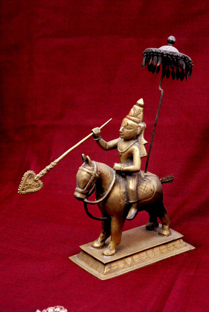 showpiece: Brass statue of king Bali raja in ancient time Hindu god showpiece on red background,Pune,Maharashtra,India
