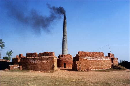 Smoke emitting out of chimney of brickyard,Village of Doulo Nangal in Amritsar,Punjab,India Stock Photo