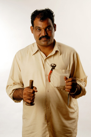 Indian man profession cobbler with tools in hand