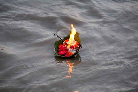 Holy offering of flowers with agarbatti and diya in Ganga river,Rishikesh,Uttaranchal,India Stock Photo