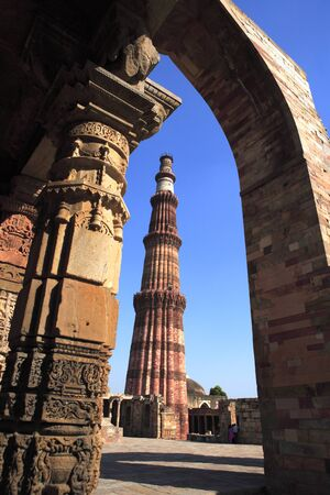 Quwwat-ul-Islam mosque and Qutab Minar through arch built in 1311 red sandstone tower,Delhi,India UNESCO World Heritage Site