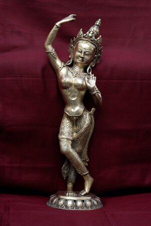 Brass statue of Thai goddess showpiece on red background,Maharashtra,India