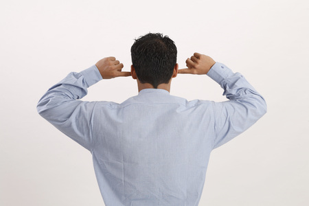 Businessman closing his both ears with both index fingers for sound pollution or does not want to hear Stockfoto