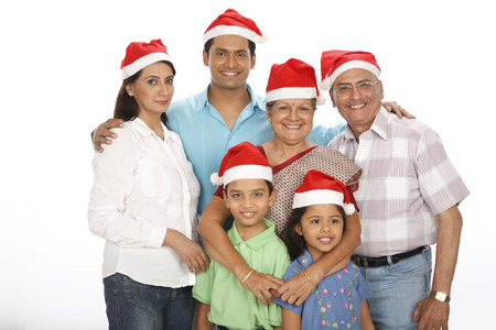 Parent children with grandparent standing together wearing Santa clause caps Stock Photo