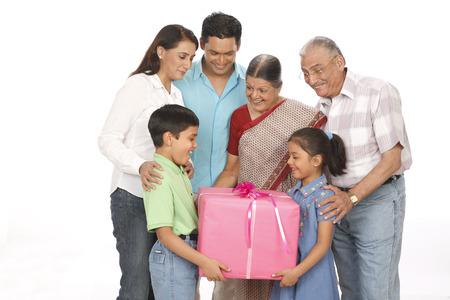 Parent children with grandparent holding gift box