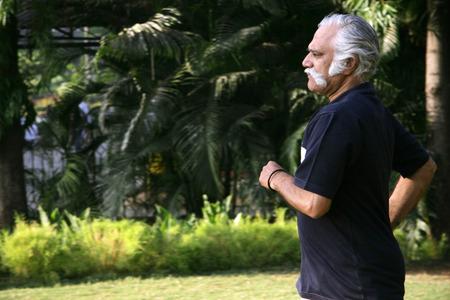 Älterer Herr über sechzig Jahren alt im dunkelblauen T-Shirt, das in einem Park joggt, um sich fit zu halten Standard-Bild