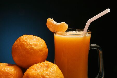 Fruit,oranges and a piece of orange fixed in the glass of orange juice against blue black background Stock Photo