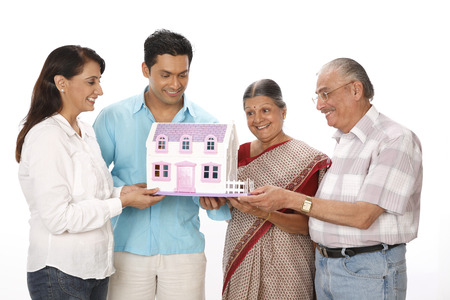 Young man woman with old parent looking at dream house model