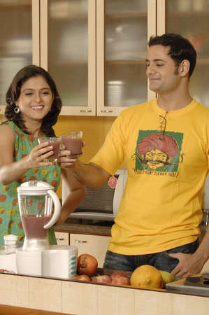 Indian lady and man touching juice glasses doing cheers in well equipped kitchen in house,Bombay Mumbai,Maharashtra,India LANG_EVOIMAGES