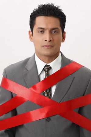 Businessman tied with red ribbon Reklamní fotografie