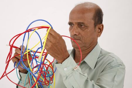Old man looking at entangled color cables and trying to separate from each other Stock Photo
