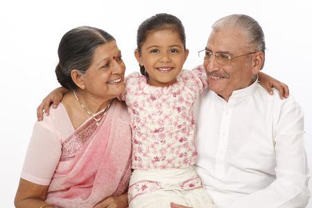 Granddaughter sitting between grandparent kept hand on their shoulders