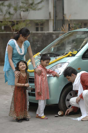 South Asian Indian modern parent with children welcoming new car traditionally Stock Photo