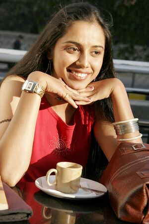Indian teenage girl drinking hot espresso coffee at wayside restaurant Stock Photo