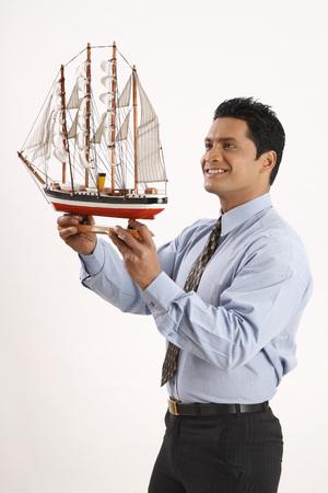 showpiece: Businessman holding miniature ship in both hands LANG_EVOIMAGES