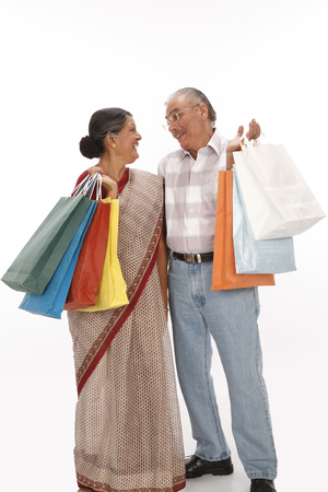 Old man and woman holding colourful shopping bags looking at each other Stock Photo