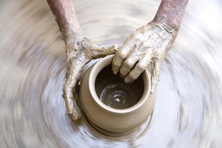 Pottery,artist muddy hands making clay pot giving shape on spinning wheel,semi urban village Dilwara,Udaipur,Rajasthan,India
