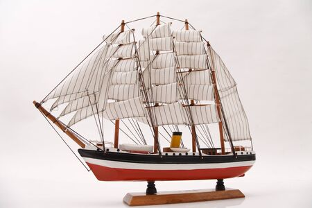 showpiece: Miniature toy sailing boat on white background LANG_EVOIMAGES