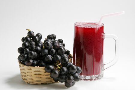 Fruit,black grapes and glass of grape juice against white background Stock Photo
