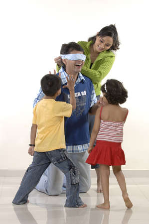 South Asian Indian modern parent playing blindfold game with children