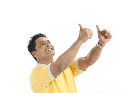 Confident young man doing winning action enjoying success by making fist of both hands and raising upwards Stock Photo