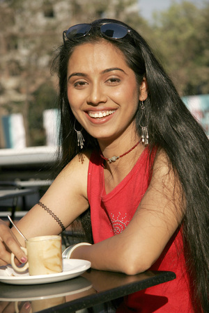Indian teenage girl enjoying cup of espresso coffee at wayside restaurant Stock Photo