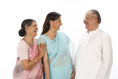 Young woman standing between old couple everyone laughing