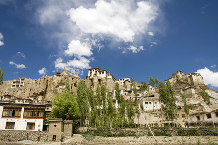 Lamayuru Buddhist Monastery rising above mass of eroded cliffs on Leh Kargil road with Poplar and Willow trees in the foreground,Ladakh,Jammu and Kashmir,India Stock Photo