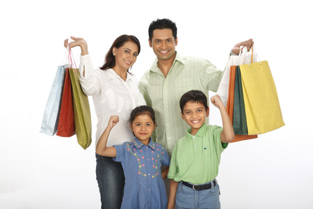 Parent,showing,colourful,shopping,bags,standing,with,children