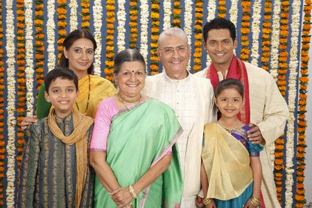 Ouderkinderen met grootouder in traditioneel dragen samen staan Stockfoto