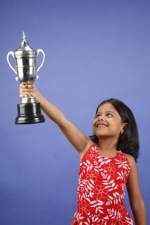 Eight year old girl raising trophy