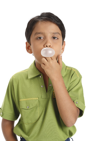 Ten year old boy blowing bubble gum covering his mouth  版權商用圖片
