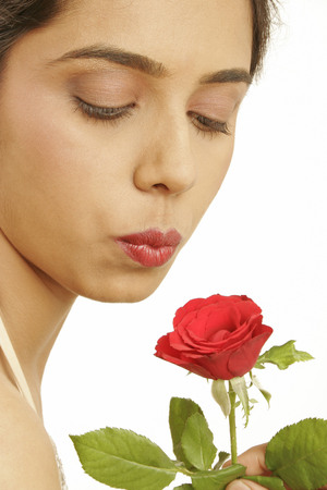 South Asian Indian teenage girl trying to give kiss to red rose