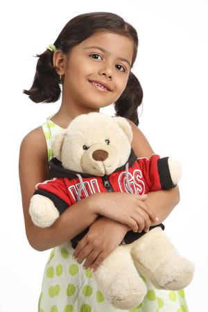 両方の手にテディベアのクマを保持している8歳の少女