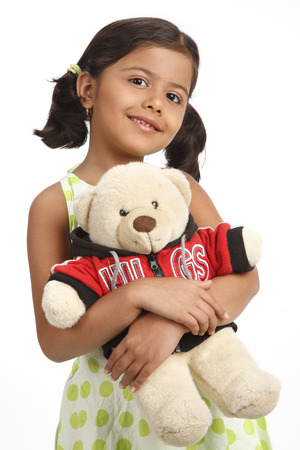 Eight year old girl holding teddy bear in both hand