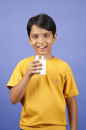 Ten year old boy holing glass of milk